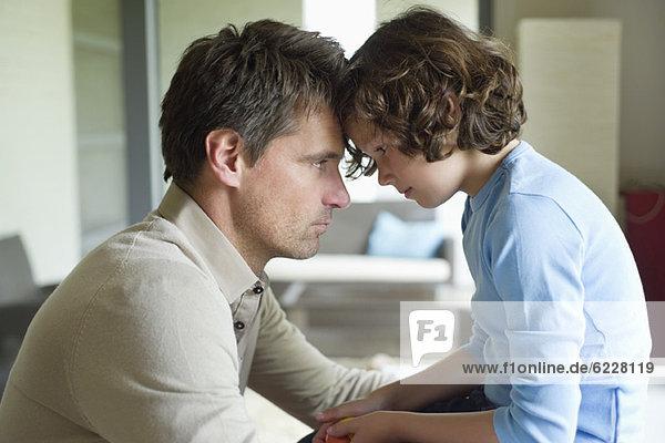 Mann mit seinem Sohn von Angesicht zu Angesicht und sieht ernst aus.
