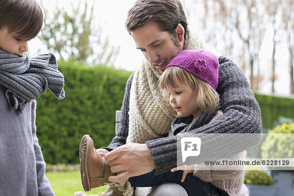 Man putting on shoe to his daughter