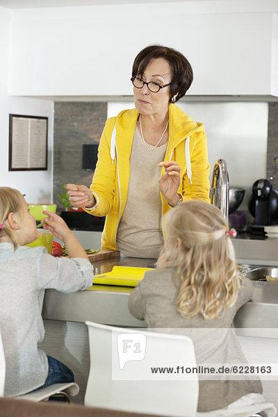Ältere Frau mit ihren Enkelinnen in der Küche