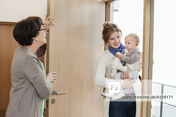 Woman with her daughter standing at the doorway