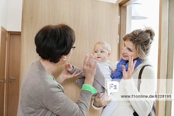 Frau winkt ihrer Tochter und Enkelin zu.