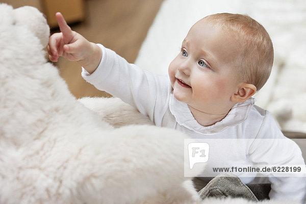 Nahaufnahme eines kleinen Mädchens  das mit einem Teddybären spielt.