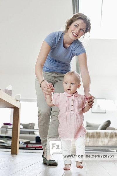Mutter hilft dem Baby beim Laufen