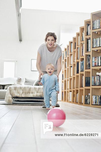 Frau spielt mit ihrer Tochter und geht auf einen Ball zu.