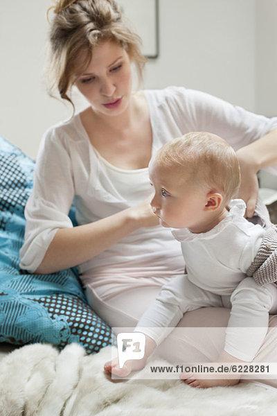 Frau  die ihrer Tochter Kleidung anzieht.