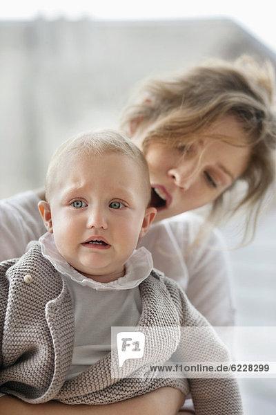 Frau tröstet ihr weinendes Baby