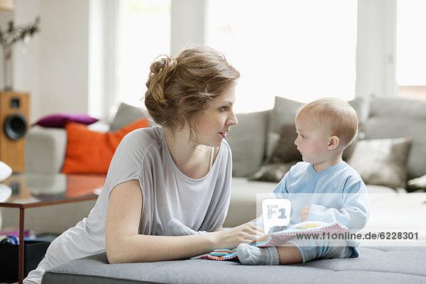 Frau unterrichtet ihre Tochter mit einem Bilderbuch