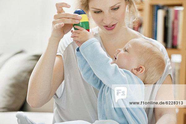 Mädchen spielt mit einem Spielzeug  das von ihrer Mutter gehalten wird.