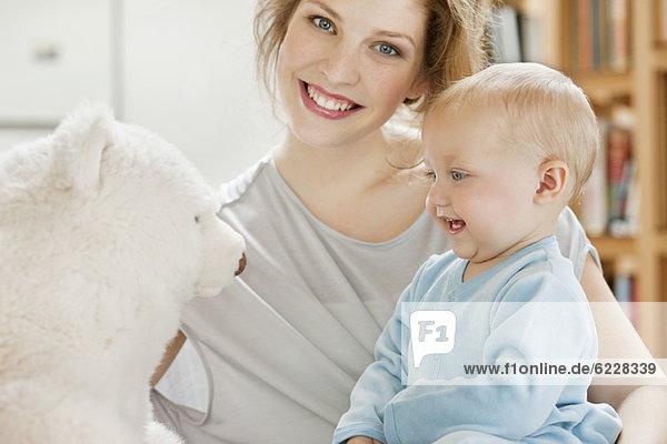 Baby Mädchen spielt mit einem Teddybär und lächelt