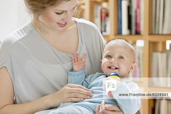 Kleines Mädchen  das auf dem Schoß seiner Mutter sitzt und mit einem Spielzeug spielt.