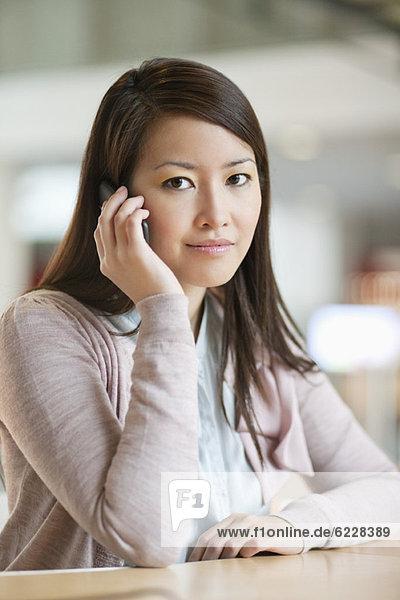 Porträt einer Geschäftsfrau  die auf dem Handy im Büro spricht