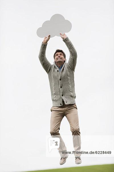 Mann  der eine Gedankenblase in einem Feld hält.