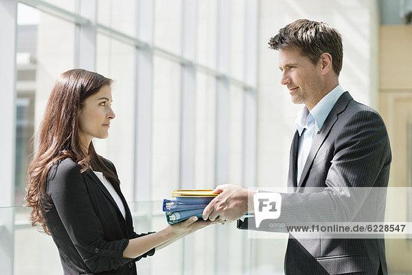 Geschäftsleute  die ihrer Kollegin in einem Büro Akten geben.