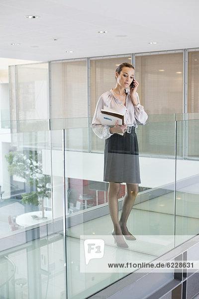 Geschäftsfrau spricht auf dem Handy in einem Büroflur