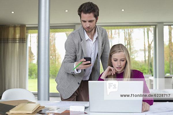 Frau arbeitet an einem Laptop mit einem Mann  der neben ihr ein Handy benutzt.