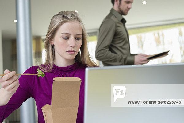 Geschäftsfrau bei der Arbeit im Home-Office mit Salat