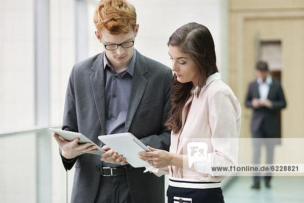 Geschäftsleute mit digitalen Tabletts im Büro