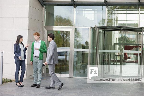 Geschäftsleute rauchen vor einem Bürogebäude