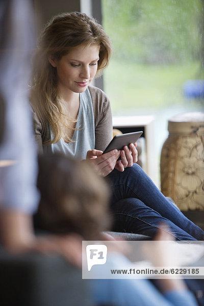 Frau liest elektronisches Buch mit ihren Kindern zu Hause