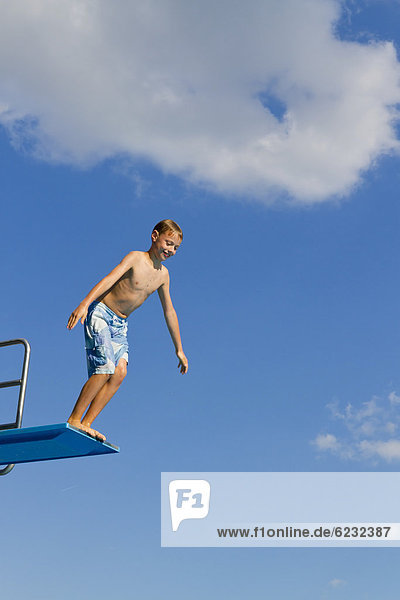 Boy jumping from the three-metre diving board at an outdoor swimming pool