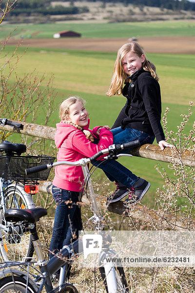 Zwei Mädchen mit Fahrrädern in ländlicher Umgebung