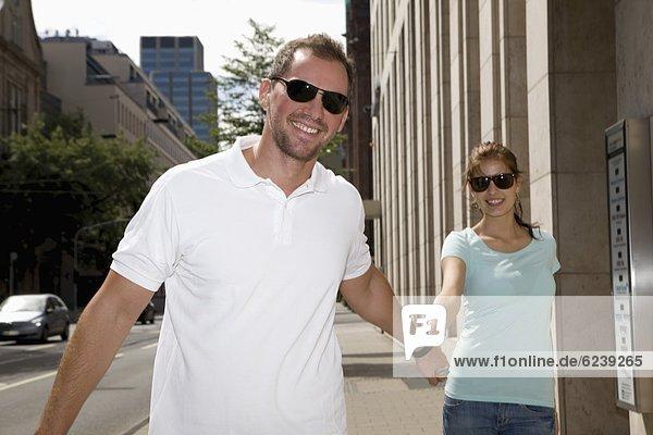 Lächelndes junges Paar mit Sonnenbrillen geht Hand in Hand auf dem Bürgersteig