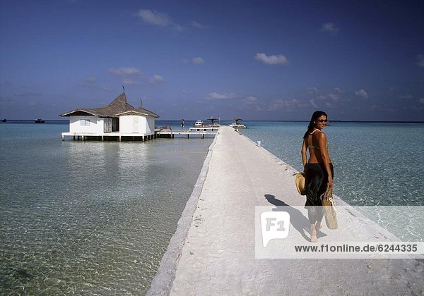 Woman on the pier of the atoll of Rhiveli  Maldives  Indian Ocean  Asia