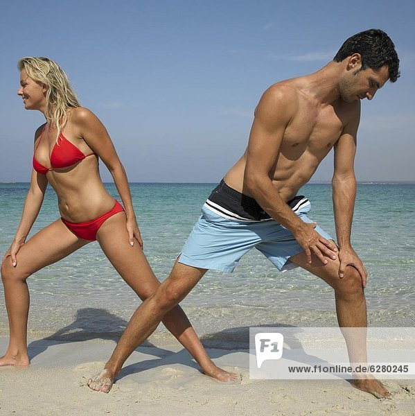 Couple on beach doing stretching exercises