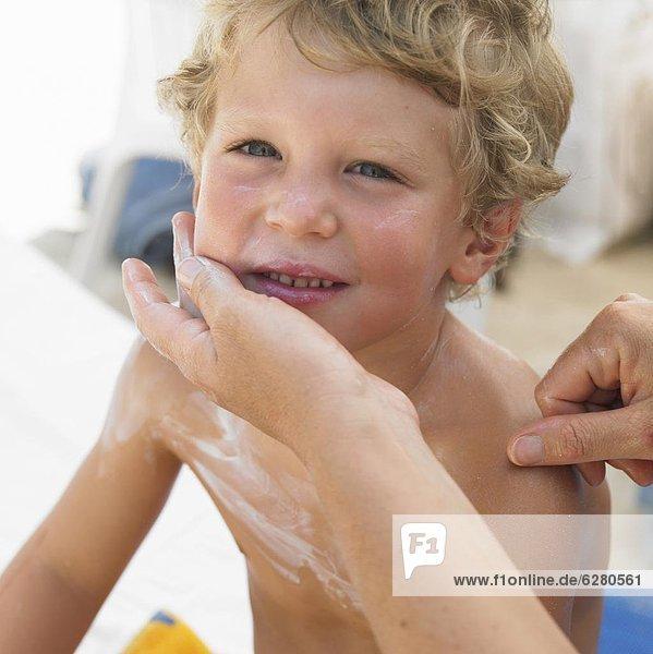 Strand  Junge - Person  eincremen  verteilen  Sonnencreme