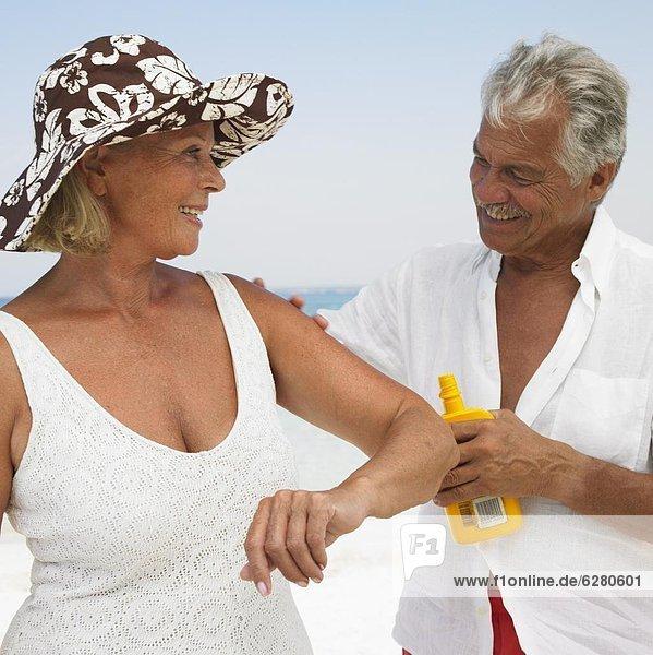 Senior couple on beach  man applying suncream to woman