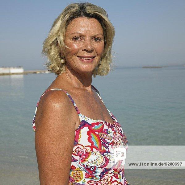 Senior woman on beach with arms raised