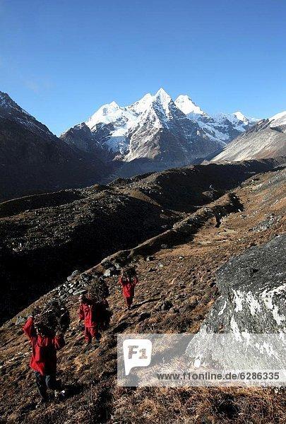 Feuerholz hoch oben Berg tragen über Dorf 3 fünfstöckig Buddhismus Himalaya Mönch