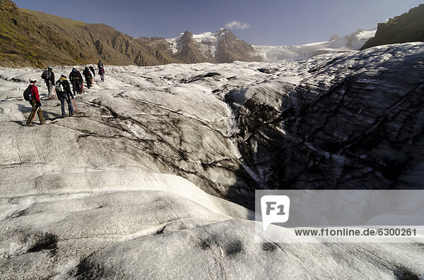 A group of hiking tourists  Svinafellsjoekull glacier tongue  Skaftafell National Park  Austurland  eastern Iceland  Iceland  Europe