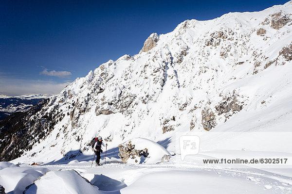Skitourengeher beim Aufstieg zum Zendleser Kofel im Villnösstal oberhalb der Zanser Alm  hier oberhalb der Wörndle-Loch-Alm  hinten die Aferer Geisler  Südtirol  Italien  Europa