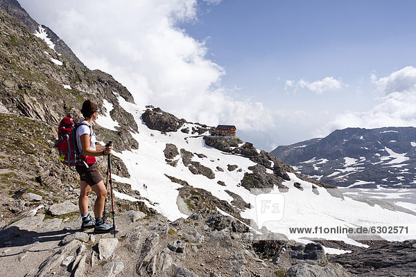 Hiker walking on the Merano High Mountain Trail near Eisjoechl  view during the ascent to Hohe Wilde mountain in the Pfossental valley  Stettiner Huette mountain lodge at the back  Schnalstal valley  province of Bolzano-Bozen  Italy  Europe
