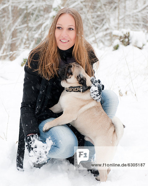 Young woman with pug dog in snow