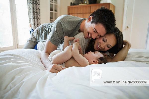 liegend  liegen  liegt  liegendes  liegender  liegende  daliegen  Junge - Person  Menschlicher Vater  Bett  Mutter - Mensch  Baby