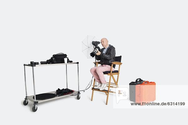 sitzend  Senior  Senioren  sehen  Stuhl  Blick in die Kamera  Fotoapparat  Kamera  Fotograf  Studioaufnahme  Regiestuhl
