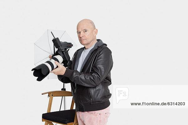 stehend Senior Senioren halten Fotoapparat Kamera Fotograf Studioaufnahme
