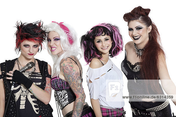 Portrait of all female rock band with microphone over white background