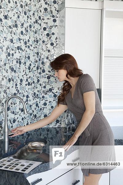 junge Frau junge Frauen Wasserhahn sehen Wohnhaus Modell Küche