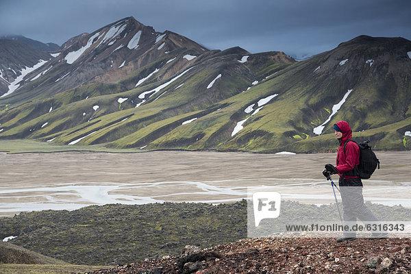 Female hiker with hiking sticks  JoekulgilskvÌsl river  snow-caped rhyolite mountains  Landmannalaugar  Fjallabak Nature Reserve  Highlands  Iceland  Europe
