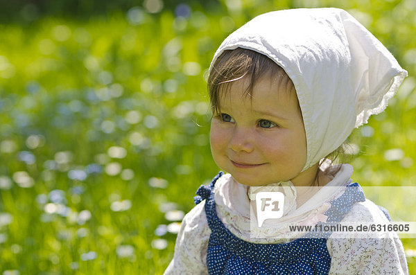 Smiling girl  nine months  in a meadow with yellow dandelions  Dresden  Germany  Europe