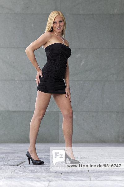 Lächelnde junge Frau mit kurzem schwarzem Kleid und hochhackigen Schuhen