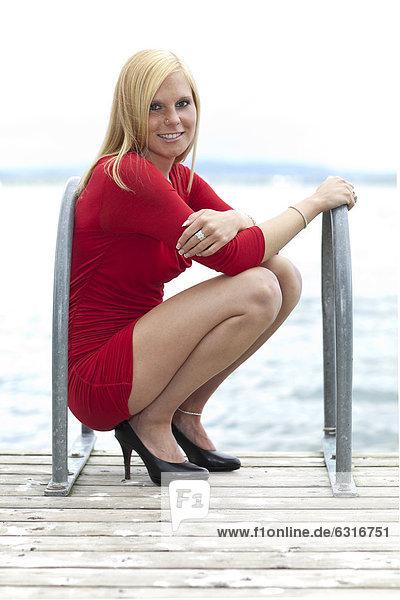 Lächelnde junge Frau mit kurzem rotem Kleid auf Holzsteg