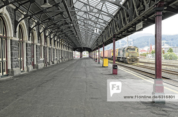 Bahnsteig mit einfahrendem Zug  historisches Bahnhofsgebäude  Dunedin  Südinsel  Neuseeland  Ozeanien