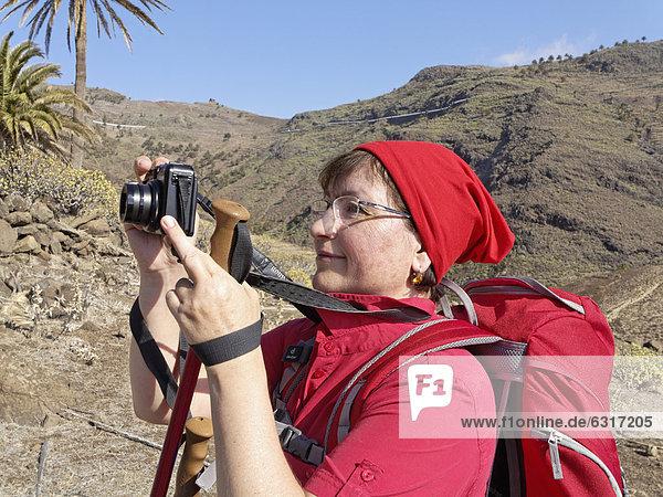 Female hiker taking a picture with a small digital camera  Barranco de la Guancha  La Gomera  Canary Islands  Spain  Europe