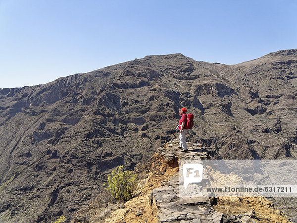 Female hiker standing on rocks  above the Barranco Juan del Vera  San Sebastian  La Gomera  Canary Islands  Spain  Europe