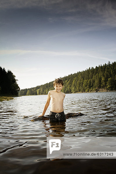Boy playing with driftwood in a lake