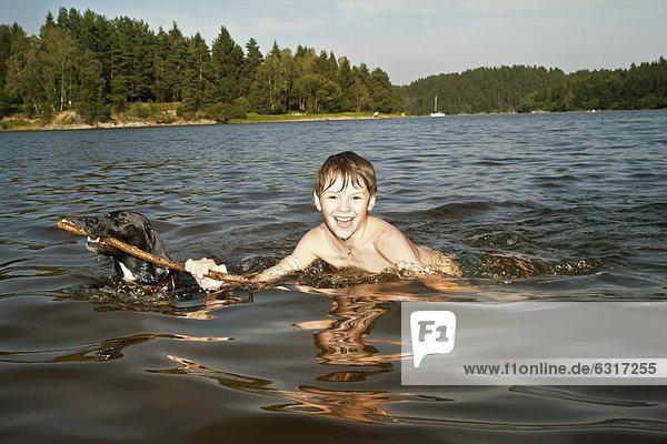 Junge spielt im See mit seinem Jagdhund